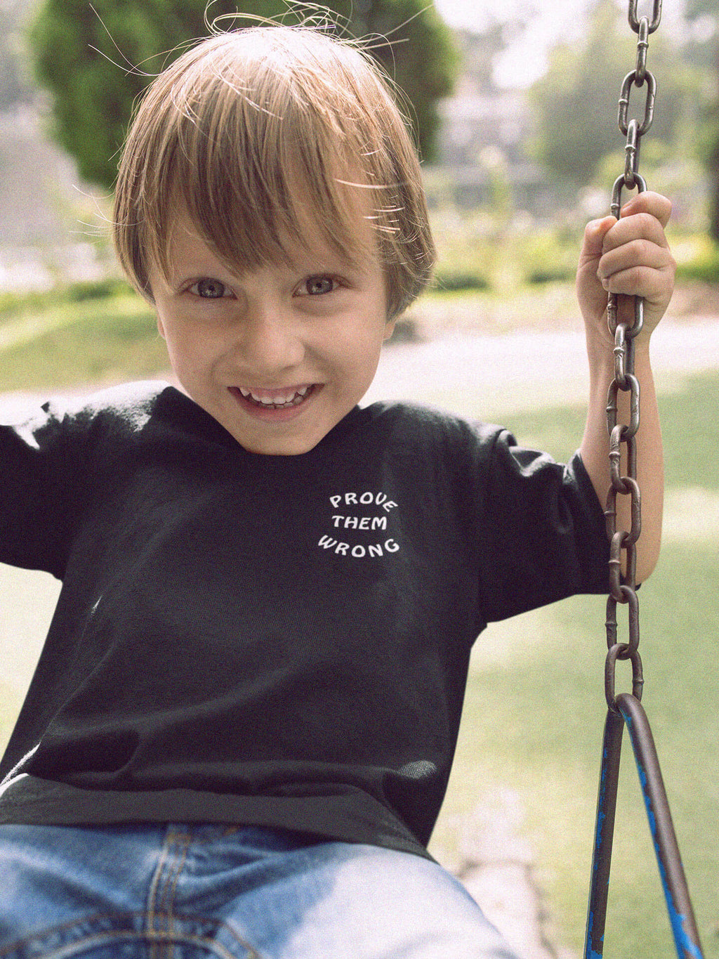 kid wearing prove them wrong t-shirt on swing