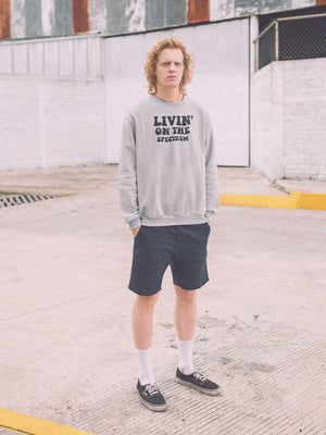 man wearing livin on the spectrum sweatshirt standing