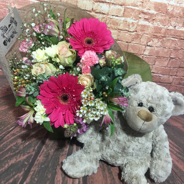 Cute and cuddly teddy with flowers
