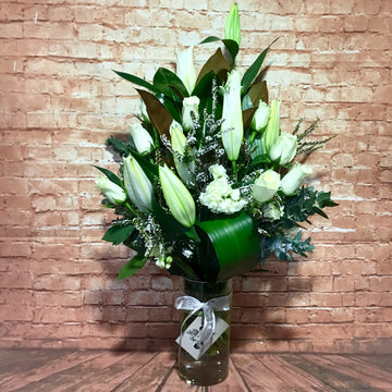 A touch of simplicity with roses and lilies in a vase.