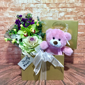 Baby hamper with flowers, teddy and chocolates.