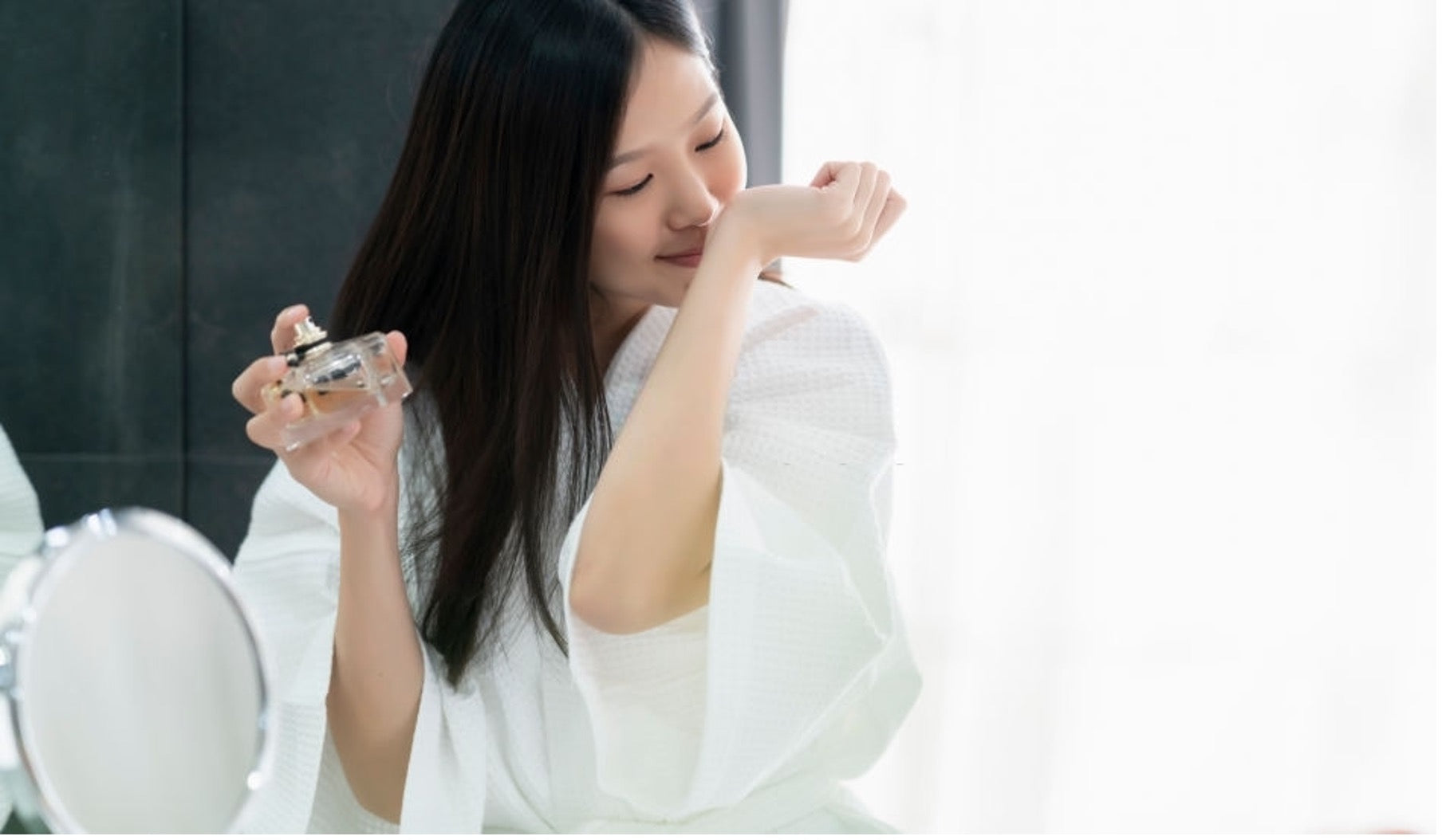 an Asian girl is smelling essential oil