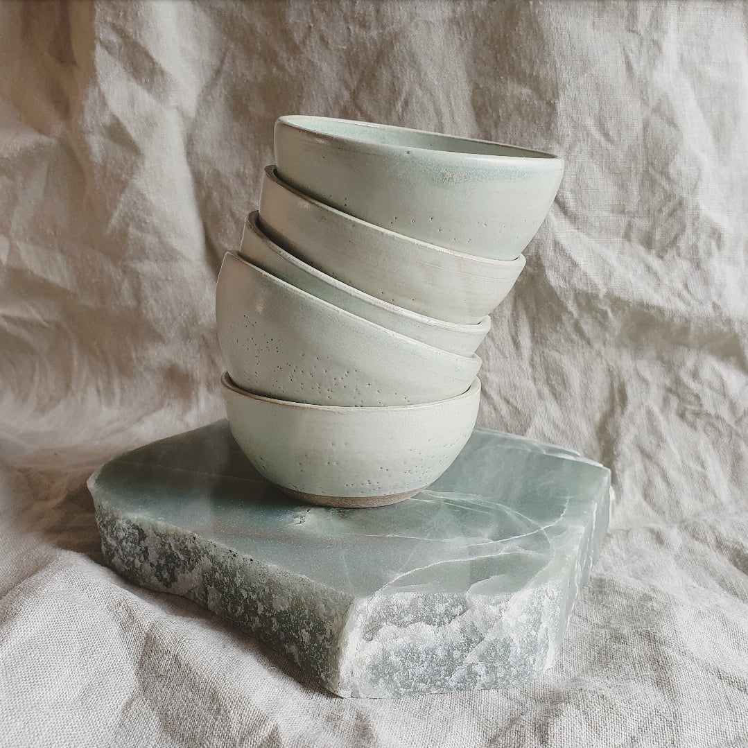 5 wonkily stacked bowls on top of flat smooth raw stone.