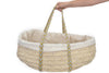 A woman holding Legacy Handwoven Palm Leaf Organic Bassinet