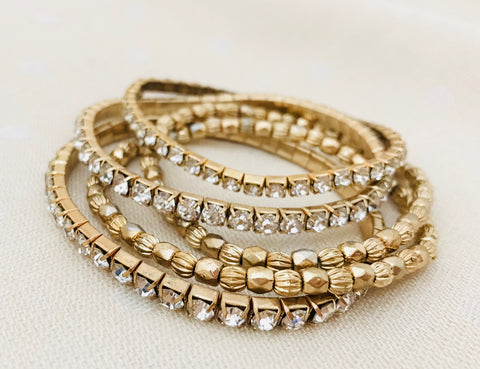 Gold bead bracelet with crystal details on a stretch cord. Stack of five bracelets.