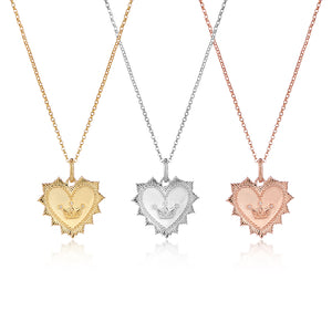 Gold medallion heart pendant with crown symbol on chain