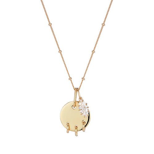 Gold disc pendant with piercing detail and marquise crystal charm pendant set on chain