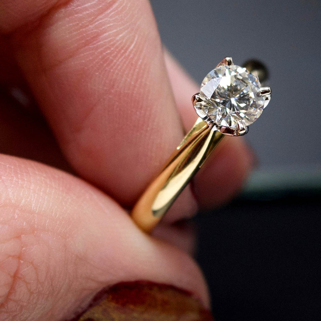 18ct Gold Petal Solitaire Diamond Engagement Ring in hand, sold at Nouveau Jewellers in Manchester