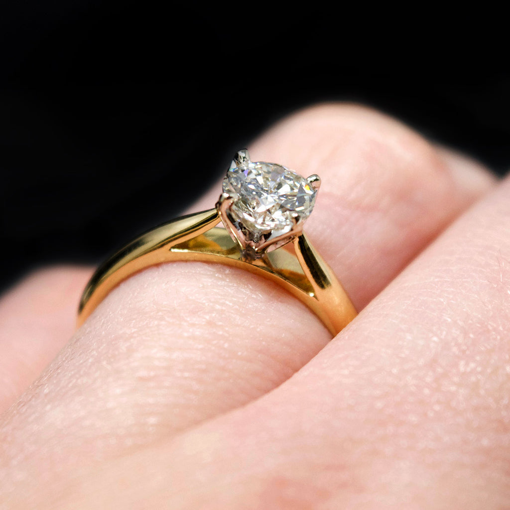 18ct Gold Petal Solitaire Diamond Engagement Ring on finger, sold at Nouveau Jewellers in Manchester