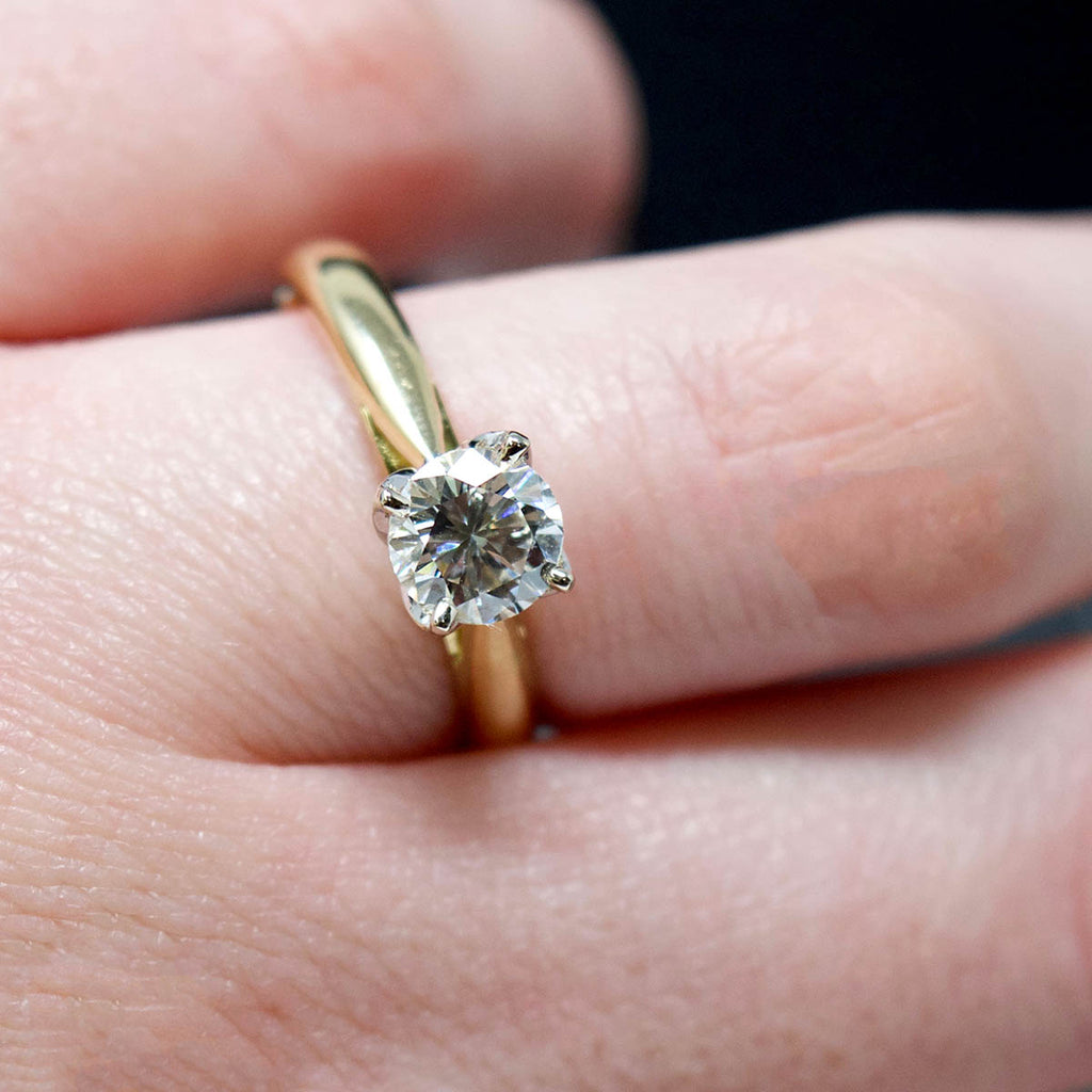 18ct Gold Petal Solitaire Diamond Engagement Ring close up on finger, sold at Nouveau Jewellers in Manchester