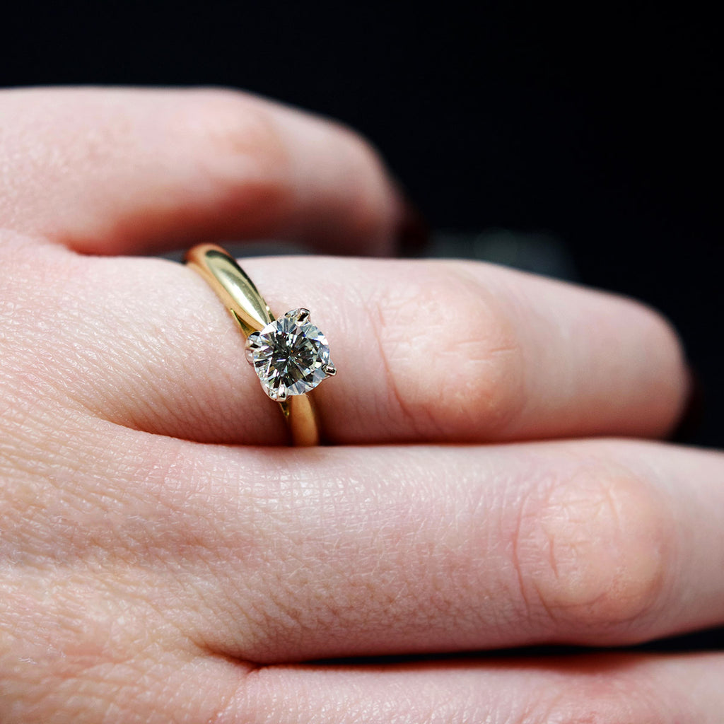 18ct Gold Petal Solitaire Diamond Engagement Ring on finger side profile, sold at Nouveau Jewellers in Manchester