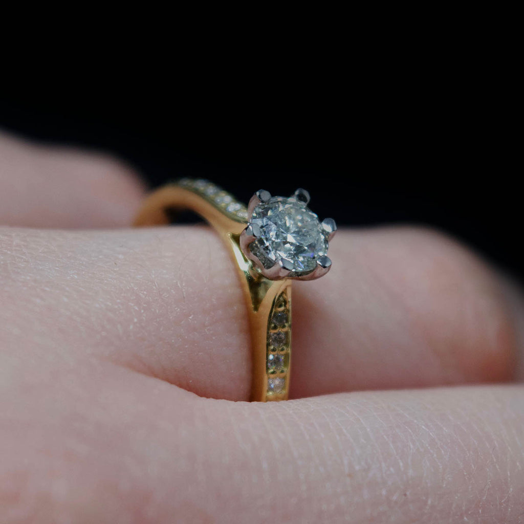 18ct Yellow Gold Solitaire Diamond Engagement Ring with Diamond Shoulders on finger, sold at Nouveau Jewellers in Manchester