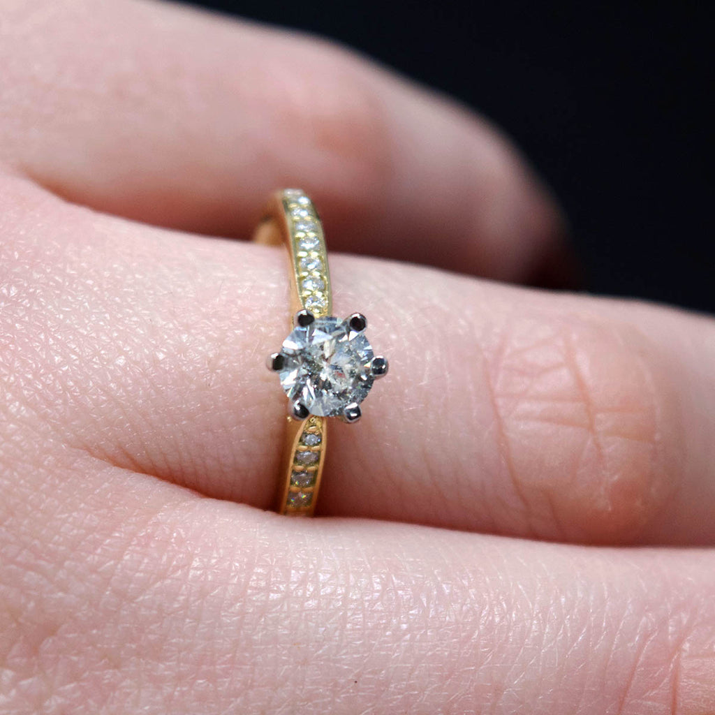 18ct Yellow Gold Solitaire Diamond Engagement Ring with Diamond Shoulders on hand, sold at Nouveau Jewellers in Manchester