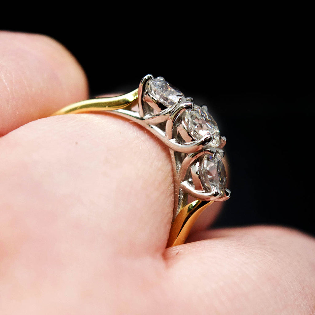 18ct Yellow Gold Trilogy Diamond Engagement Ring on finger close up, sold at Nouveau Jewellers in Manchester
