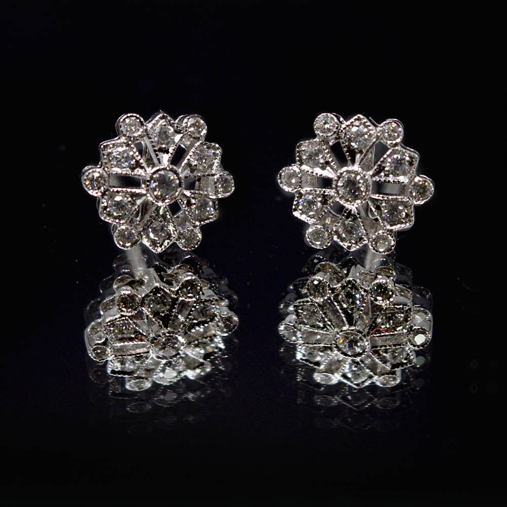 18ct White Gold Diamond Snowflake Art Deco Earrings on reflective surface, sold at Nouveau Jewellers in Manchester