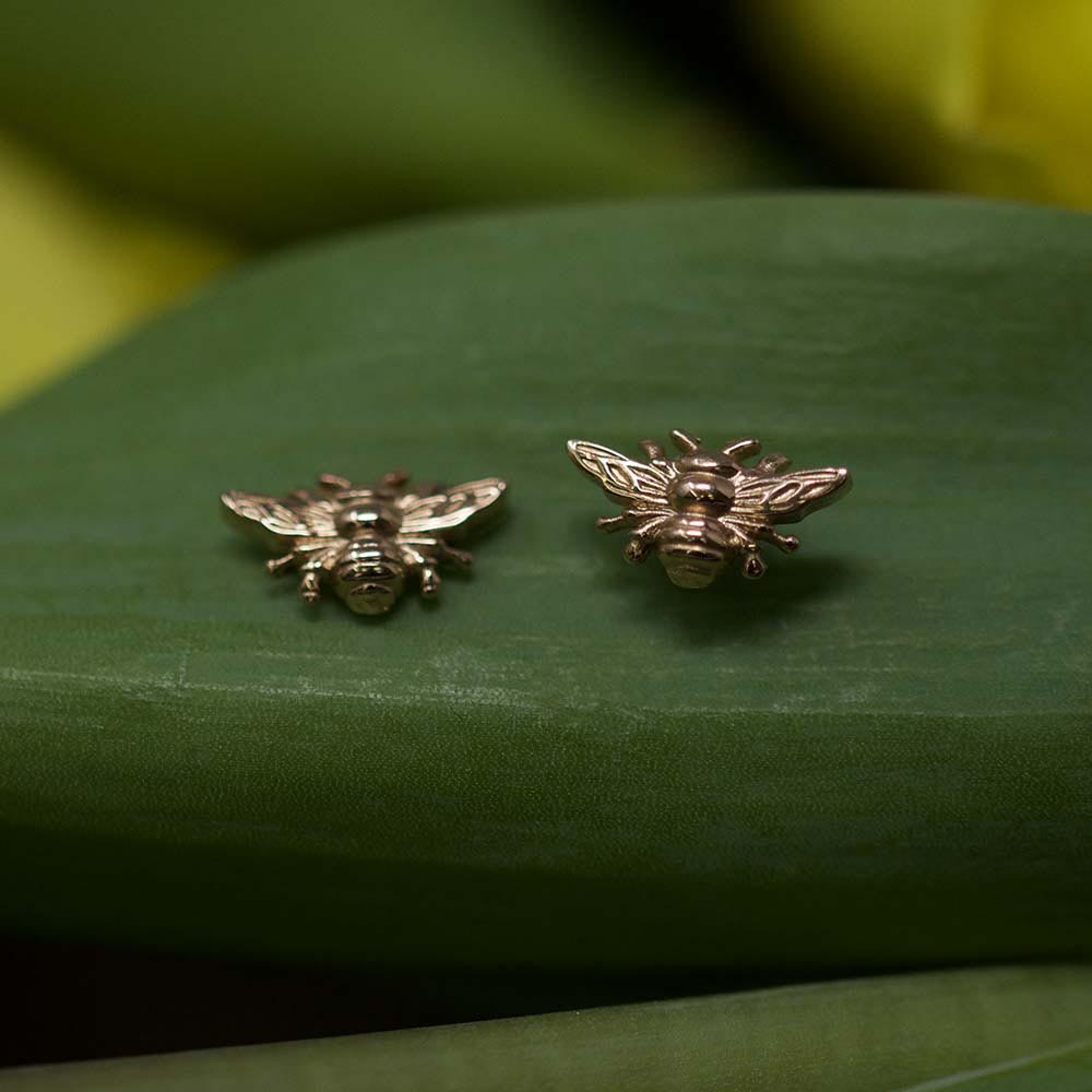 Rose Gold Manchester Bee Studs on green background, Beehive Collection exclusively sold at Nouveau Jewellers in Manchester