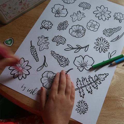 child colouring in a sheet of illustrated flowers
