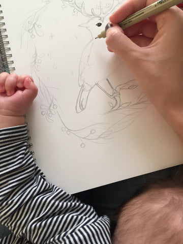 mamas hand drawing with sleeping baby
