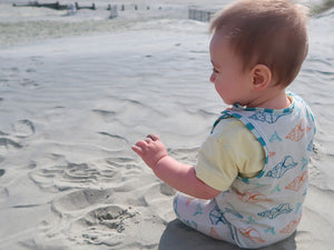 baby sits on sandy beach wearing seashell print romper