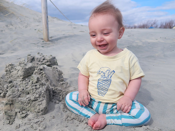 laughing baby wearing surf print top sat by a sandcastle
