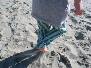 child walking on sand wearing stripy harem trousers