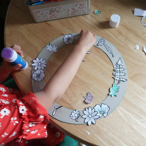 child crafting and sticking paper flowers onto a handmade cardboard wreath