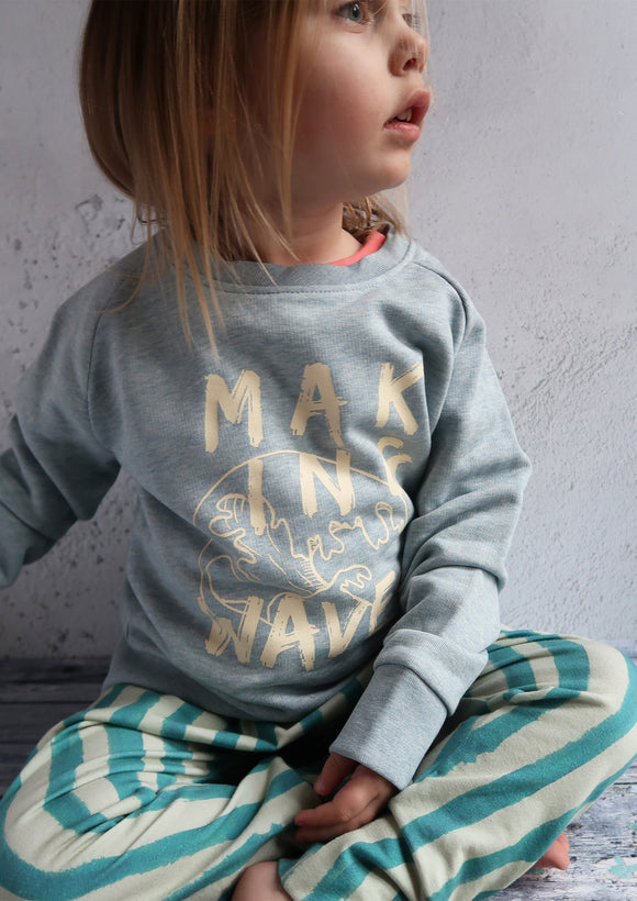little girl sitting down wearing grey slogan sweatshirt and stripy trousers
