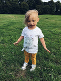 Toddler wearing floral print tshirt outdoors