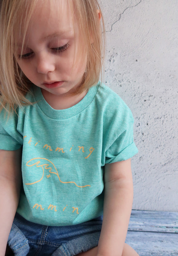 little girl in green organic slogan tee