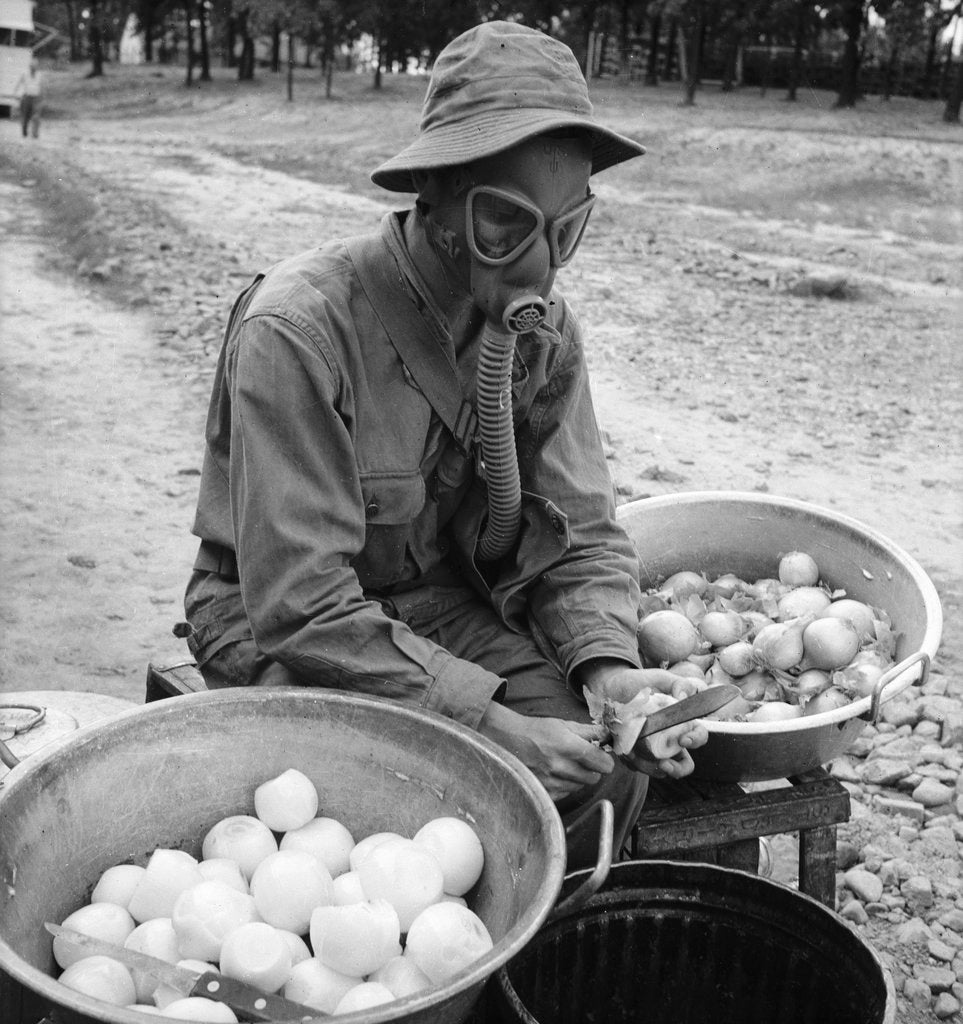 Detail of American soldier peeling onions while wearing a gas mask by Alan Villiers