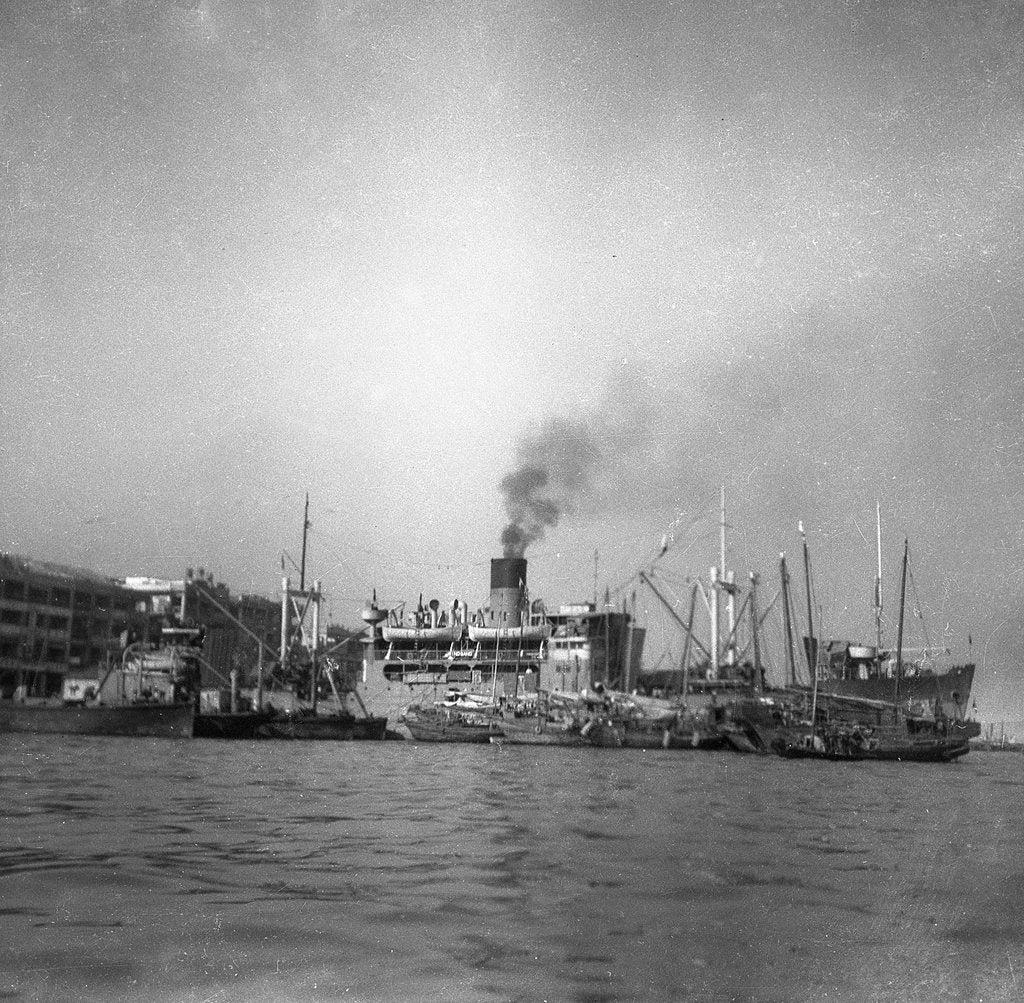 Detail of 'Wing Sang' (Br, 1938), at anchor, surrounded by small craft by unknown