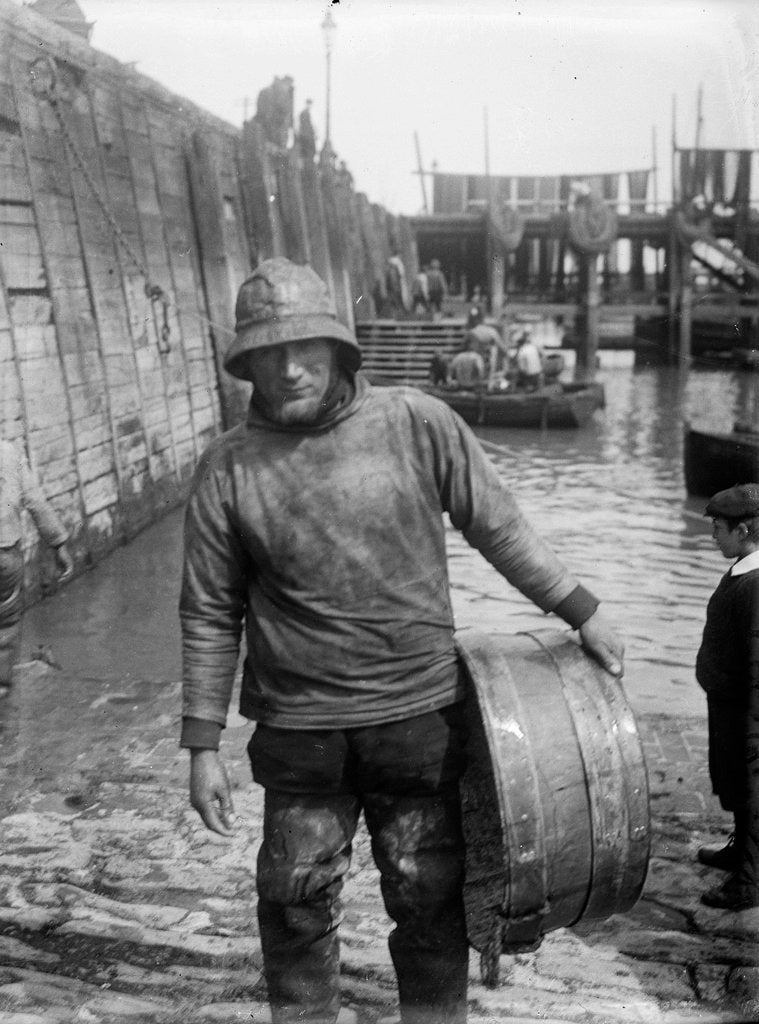 Detail of A Folkestone fisherman in smock and sou'wester carrying a tub for fish on the slipway by unknown