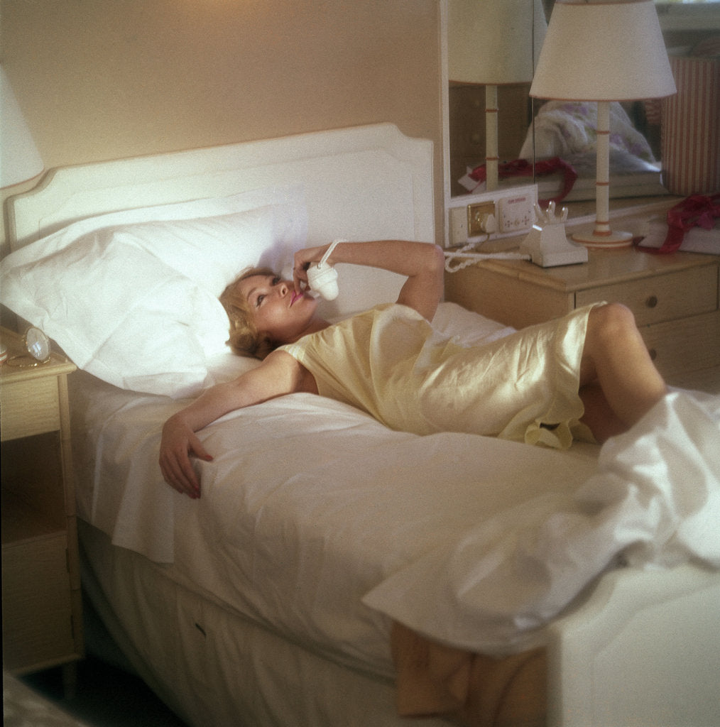 Detail of Modern convenience aboard a cruise liner: a female passenger reclines in bed whilst making a phone call; the ship and the conversation's content are unspecified by Marine Photo Service