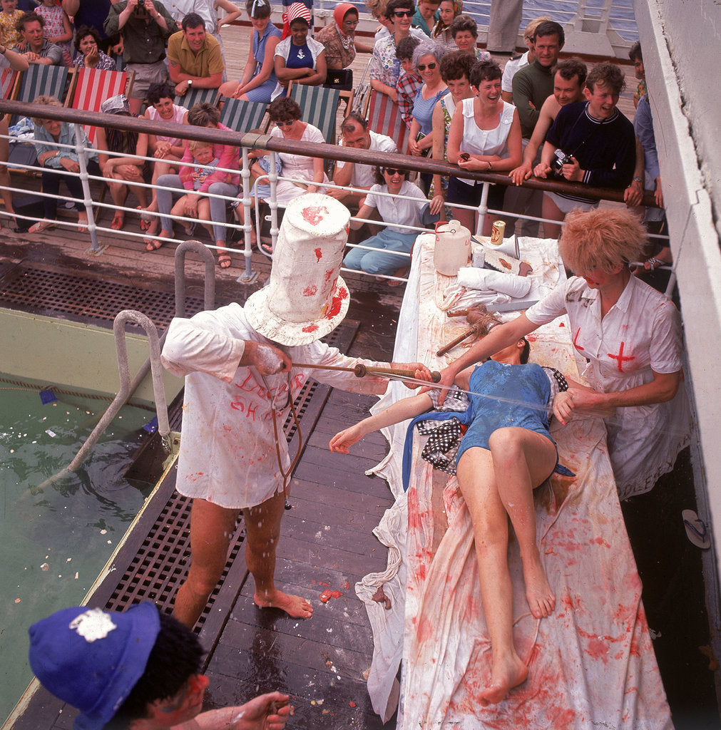 Detail of Macabre comic entertainment aboard an unspecified cruise ship, with a female passenger prostrate on a bloody slab - perhaps a variant of the Crossing the Line (the Equator) ceremony? by Marine Photo Service