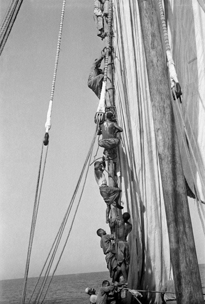 Detail of Kuwaiti sailors climbing aloft and working on the lateen yard by Alan Villiers