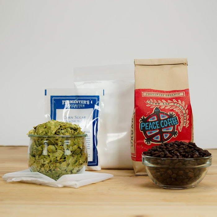 Yeti cold press peace coffee, 1-pound bag of lactose, priming sugar, cascade leaf hops, straining bag, and coffee beans in a bowl