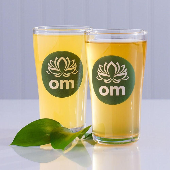 Two Everbru kombucha glasses proudly displaying their logos behind a small sprig