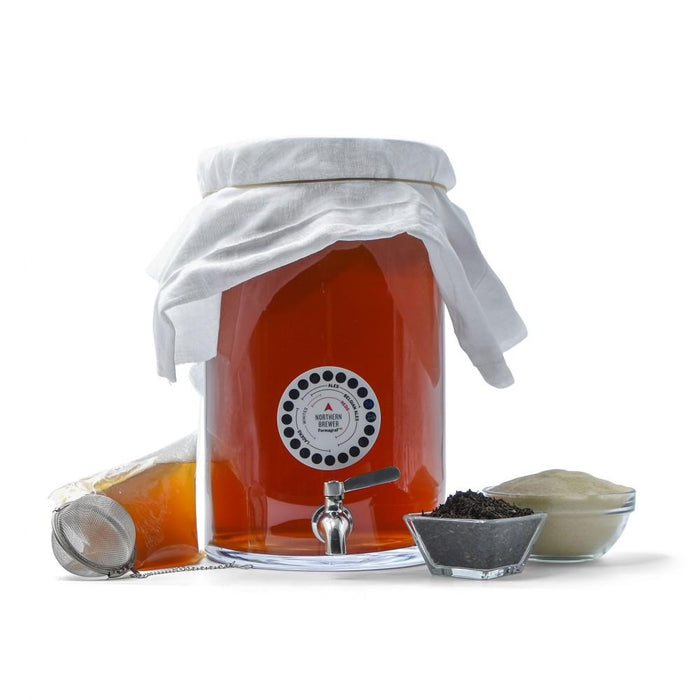 Kombucha fermenting with adhesive thermometer, stainless steel spigot, ingredients, stainless steel tea ball, and SCOBY packaging