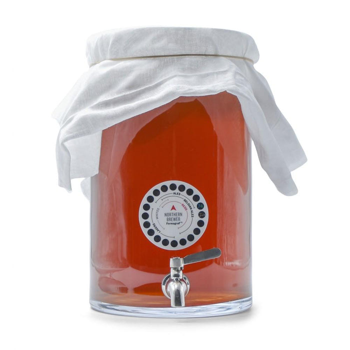 Kombucha Brewing in a glass fermenter with a stainless steel spigot, muslin cover, and adhesive thermometer attached