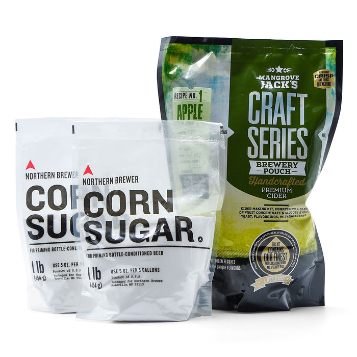 Hard peach and passionfruit cider concentrate in a pouch beside two bags of corn sugar