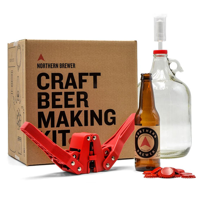 One Gallon Craft Beer Making Kit box with a red Bottle Capper, 1 Gallon Fermenter with an airlock and cap, a bottle with the northern brewer label, and a pile of bottle caps.