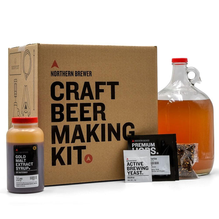 Craft beer making kit box with a container of malt extract, a packet of hops, a glass carboy filled with wort, and a cleaner packet.