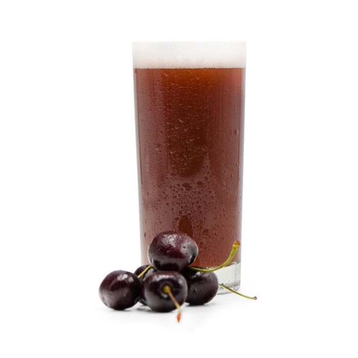 Cherries in a small pile beside a glass of Fruit Stand Wheat Beer