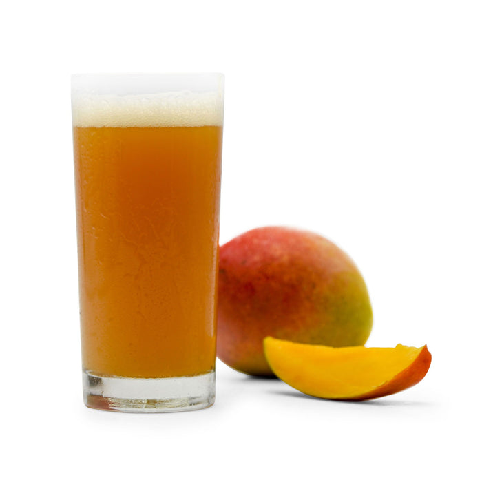 One whole and one sliced Mango next to a glass of Fruit Stand Wheat homebrew