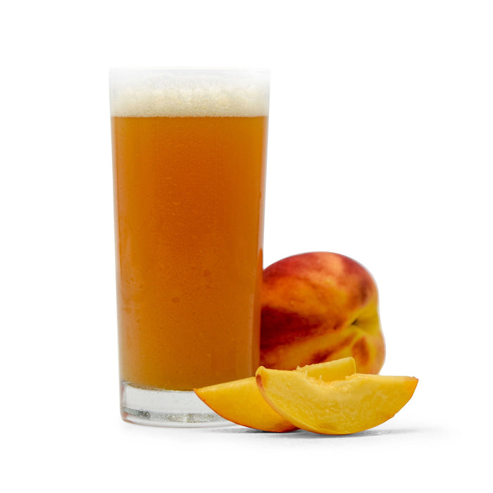 Sliced and whole Peaches next to a glsas of Fruit Stand Wheat Beer