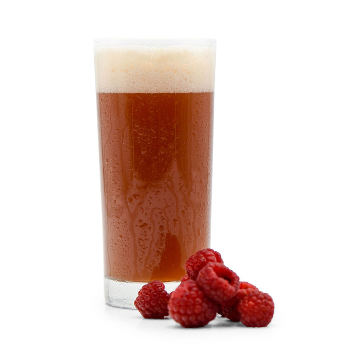 Pile of Raspberries in front of a glass of Fruit Stand Wheat Beer