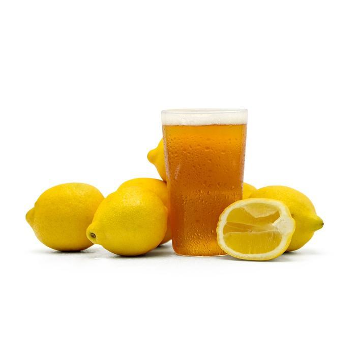 Summer Squeeze Lemon Shandy in a glass surrounded by cut lemons