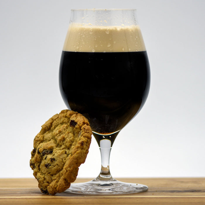Oatmeal Cookie Pastry Stout in a glass with an oatmeal cookie leaning against it