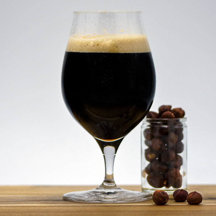 Hazelnut Pastry Stout with a glass filled with hazelnuts adjacent
