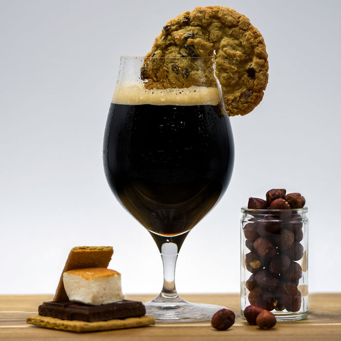 Pastry Stout homebrew in a glass with an oatmeal cookie wedge, next to a cup of hazelnuts and a fully-assembled smores bar